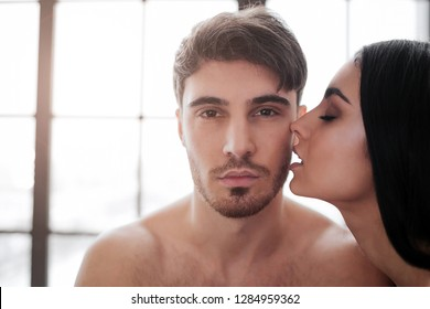 Young handsome man look on camera. Beautiful woman kiss him. Window is behind them. They are naked in room.