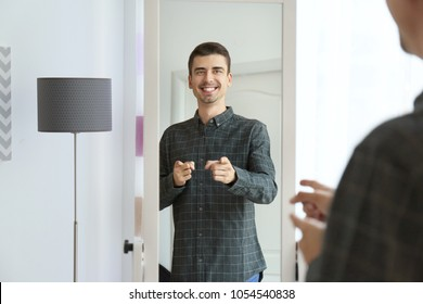 Young handsome man looking in mirror indoors