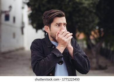 Young handsome man looks shocked, closes his mouth with his hands. A man outdoors looks scared