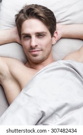Young handsome man lying in bed