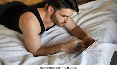 Young handsome man lying in bed and using tablet computer or reading an ebook in his bedroom at home at night - Shutterstock ID 711594427