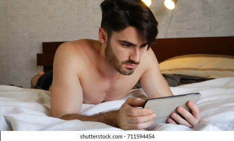 Young handsome man lying in bed and using tablet computer or reading an ebook in his bedroom at home at night - Shutterstock ID 711594454