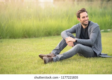 Young handsome man lying down on the green grass, enjoying a sunset relaxation in a park