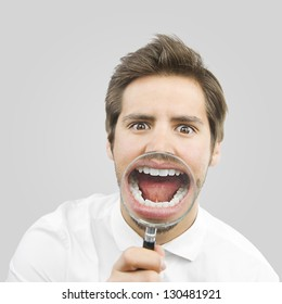 young handsome man with a magnifying glass in his mouth isolated over gray background