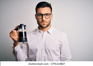 Young handsome man making coffee using french press coffeemaker over isolated background with a confident expression on smart face thinking serious