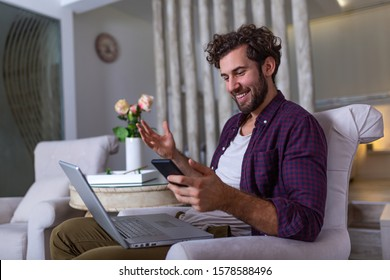 Young handsome man making video call with friends while sitting on sofa at his modern home.Concept of happy business people. Business man at home checking statistics on mobile phone and laptop