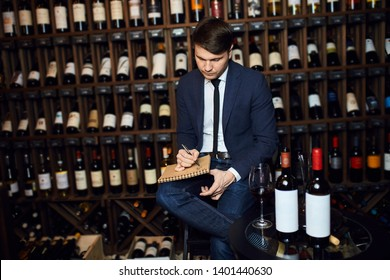 young handsome man managing the inventory of the wine cellar. close up photo