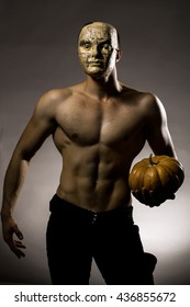 Young handsome man in mask of newspaper with muscular body bare chest and torso posing in studio holding yellow halloween pumpkin on grey background