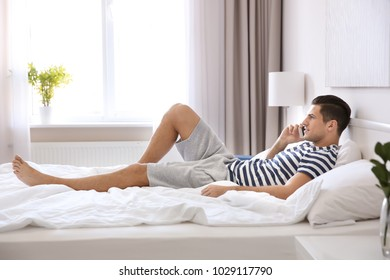 Young handsome man with mobile phone on bed at home