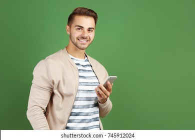 Young handsome man with mobile phone against color background