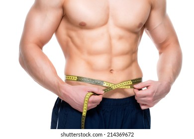 Young handsome man with a muscular torso uses measuring tape - isolated on white background.