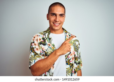 Young handsome man on holidays wearing Hawaiian shirt over white background cheerful with a smile of face pointing with hand and finger up to the side with happy and natural expression on face