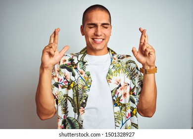 Young handsome man on holidays wearing Hawaiian shirt over white background gesturing finger crossed smiling with hope and eyes closed. Luck and superstitious concept.