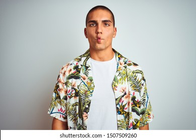 Young handsome man on holidays wearing Hawaiian shirt over white background making fish face with lips, crazy and comical gesture. Funny expression.