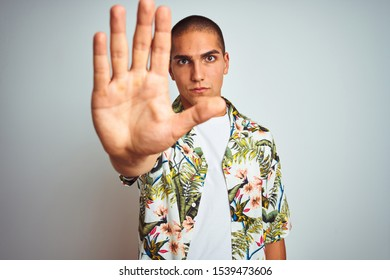 Young handsome man on holidays wearing Hawaiian shirt over white background doing stop sing with palm of the hand. Warning expression with negative and serious gesture on the face.