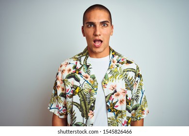 Young handsome man on holidays wearing Hawaiian shirt over white background afraid and shocked with surprise expression, fear and excited face.