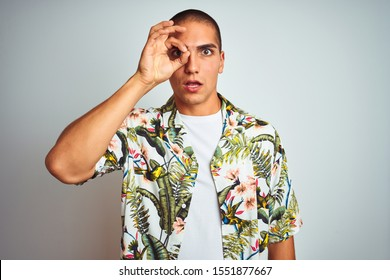 Young handsome man on holidays wearing Hawaiian shirt over white background doing ok gesture shocked with surprised face, eye looking through fingers. Unbelieving expression.