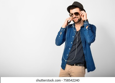 young handsome man on white studio background, isolated, listening to music on earphones, holding phone, smiling, happy