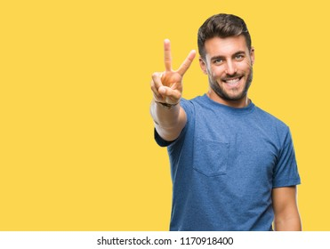 Young handsome man over isolated background smiling looking to the camera showing fingers doing victory sign. Number two.