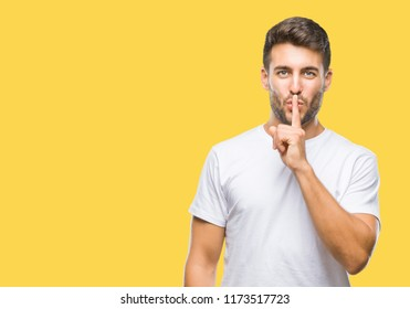 Young handsome man over isolated background asking to be quiet with finger on lips. Silence and secret concept.