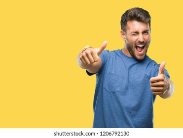 Young handsome man over isolated background approving doing positive gesture with hand, thumbs up smiling and happy for success. Looking at the camera, winner gesture.