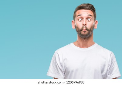 Young handsome man over isolated background making fish face with lips, crazy and comical gesture. Funny expression.