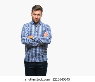 Young handsome man over isolated background skeptic and nervous, disapproving expression on face with crossed arms. Negative person.