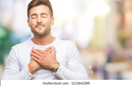 Young handsome man over isolated background smiling with hands on chest with closed eyes and grateful gesture on face. Health concept.