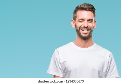Young handsome man over isolated background winking looking at the camera with sexy expression, cheerful and happy face.