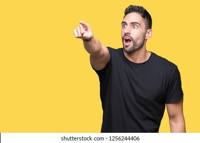 Young handsome man over isolated background Pointing with finger surprised ahead, open mouth amazed expression, something in front