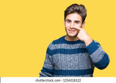 Young handsome man over isolated background Pointing with hand finger to face and nose, smiling cheerful
