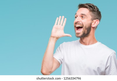 Young handsome man over isolated background shouting and screaming loud to side with hand on mouth. Communication concept.