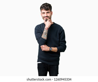 Young handsome man over isolated background looking confident at the camera with smile with crossed arms and hand raised on chin. Thinking positive.