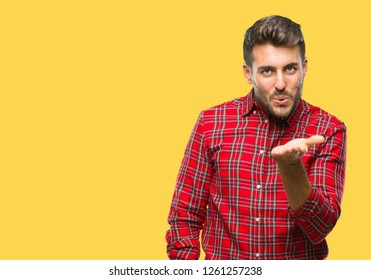 Young handsome man over isolated background looking at the camera blowing a kiss with hand on air being lovely and sexy. Love expression.