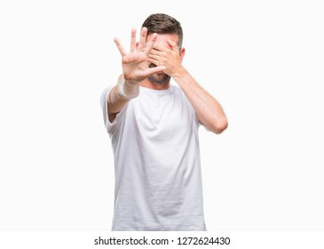 Young handsome man over isolated background covering eyes with hands and doing stop gesture with sad and fear expression. Embarrassed and negative concept.
