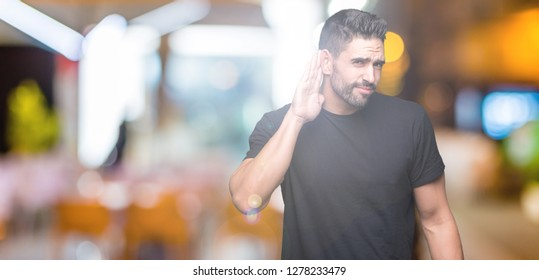 Young handsome man over isolated background smiling with hand over ear listening an hearing to rumor or gossip. Deafness concept.