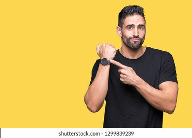 Young handsome man over isolated background In hurry pointing to watch time, impatience, upset and angry for deadline delay