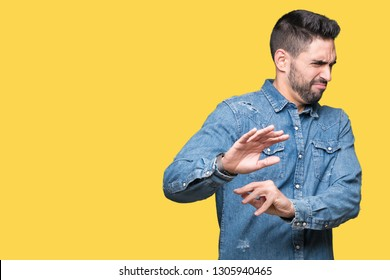 Young handsome man over isolated background disgusted expression, displeased and fearful doing disgust face because aversion reaction. With hands raised. Annoying concept.