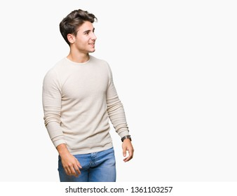 Young handsome man over isolated background looking away to side with smile on face, natural expression. Laughing confident.