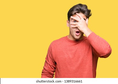 Young handsome man over isolated background peeking in shock covering face and eyes with hand, looking through fingers with embarrassed expression.