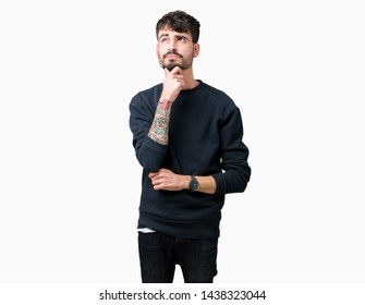 Young handsome man over isolated background with hand on chin thinking about question, pensive expression. Smiling with thoughtful face. Doubt concept.
