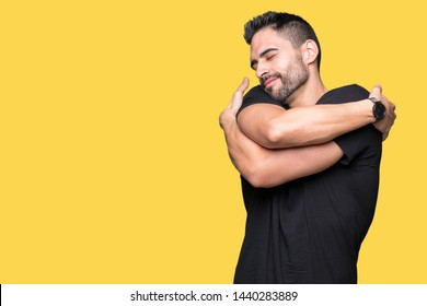 Young handsome man over isolated background Hugging oneself happy and positive, smiling confident. Self love and self care