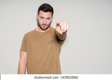 Young handsome man over isolated background pointing with finger to the camera and to you, hand sign, positive and confident gesture from the front