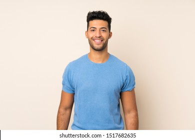 Young handsome man over isolated background keeping the arms crossed in frontal position