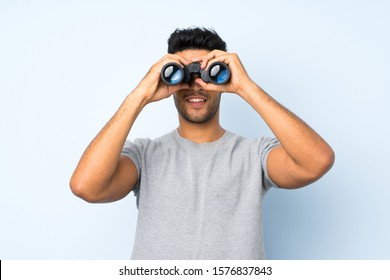 Young handsome man over isolated background with black binoculars