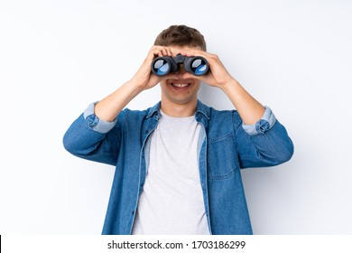 Young handsome man over isolated white background with black binoculars