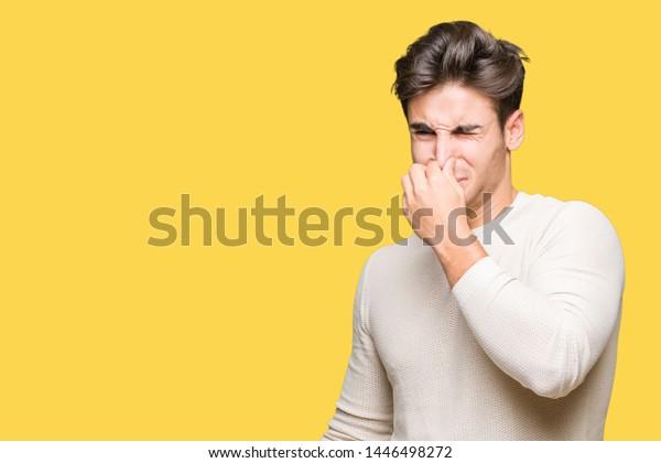 分離型背景に若いハンサムな男性が、何か臭く、嫌な匂いを嗅ぎ、鼻に指で息をつきながら。悪い匂いのコンセプト。