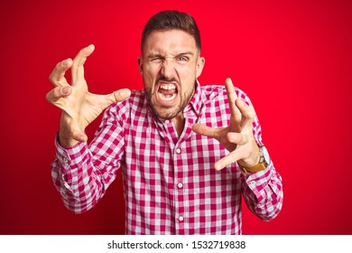 Young handsome man over red isolated background Shouting frustrated with rage, hands trying to strangle, yelling mad
