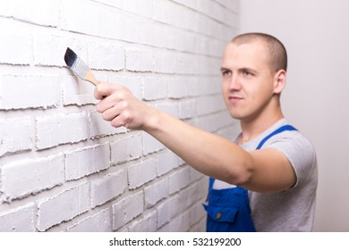 young handsome man painter in work wear painting white brick wall with paint brush