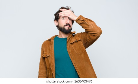 young handsome man panicking over a forgotten deadline, feeling stressed, having to cover up a mess or mistake against flat wall